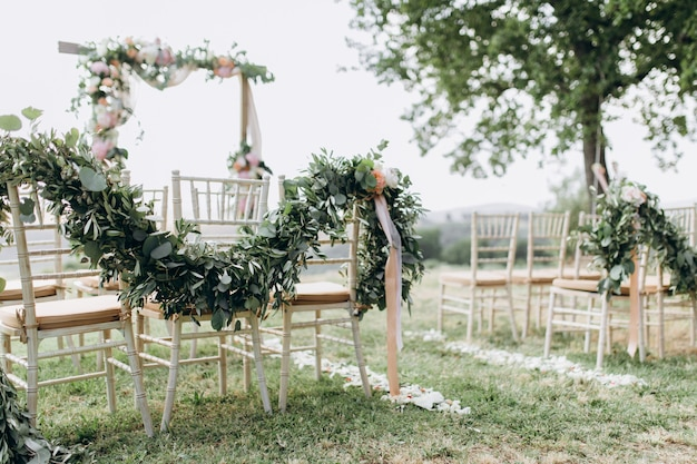 Floral compositions made of greenery at the outdoors wedding ceremony Free Photo