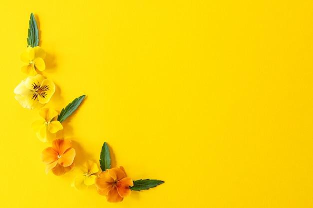 Цветочная рамка композиции. композиция из цветов анютины глазки на желтом фоне с копией пространства Premium Фотографии