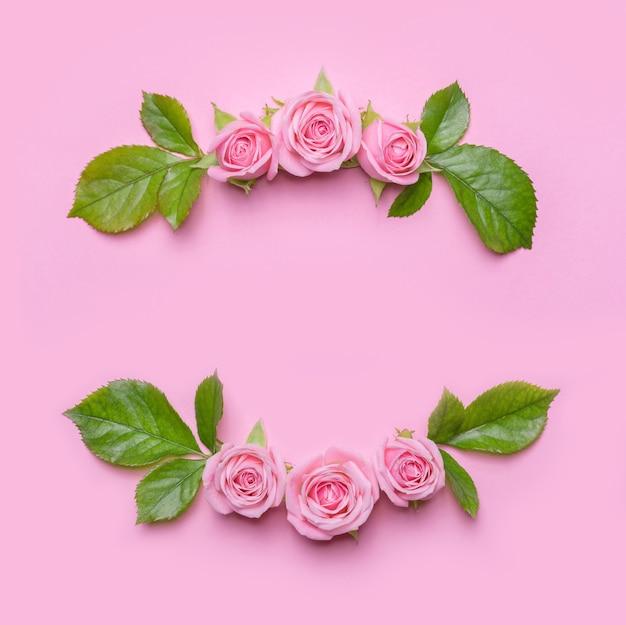 핑크 바탕에 핑크 장미와 꽃 프레임. 꽃의 테두리. 초대 카드 패턴입니다. 평면 위치 디자인, 위에서보기 프리미엄 사진