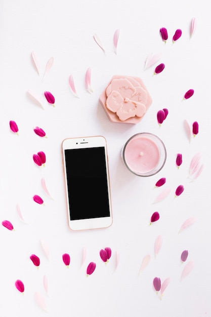 Floral soap; candle and smartphone decorated with flower petals on white background Free Photo