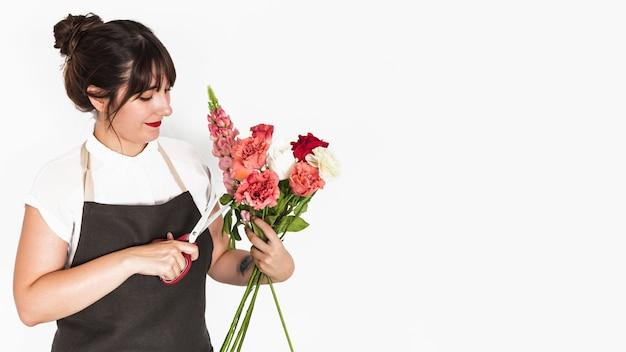 Fiorista taglio ramoscelli di fiori con le forbici su sfondo bianco Foto Gratuite