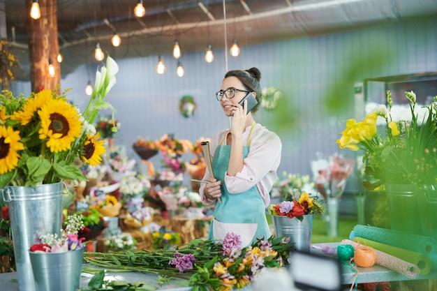 Florist talking by smartphone in shop Premium Photo