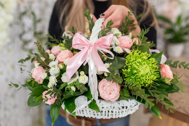 Florist woman holding a beautiful bouquet of roses in white basket Premium Photo