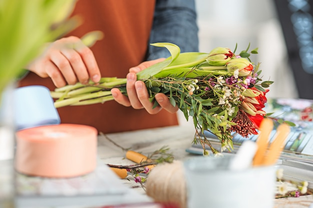 Florist at work: the female hands of woman making fashion modern bouquet of different flowers Free Photo