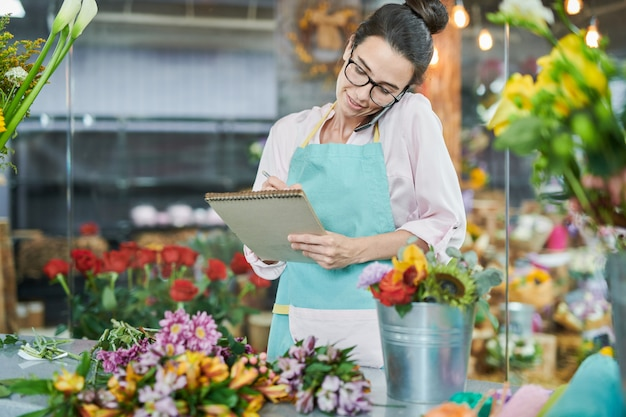 Florist writing notes talking by smartphone Premium Photo