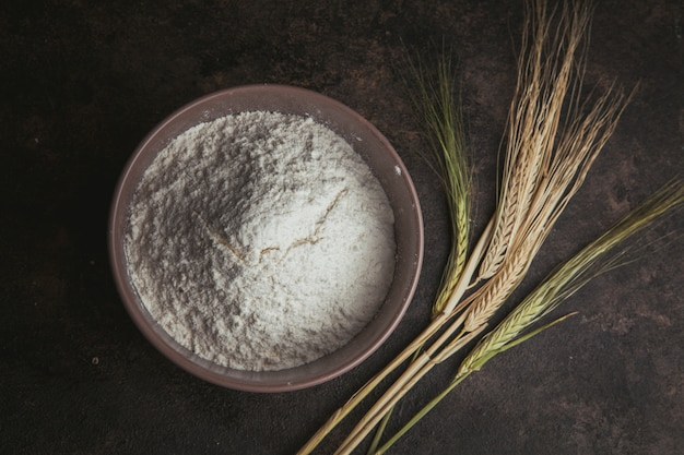 Flour in a bowl with wheat flat lay on a dark brown Free Photo