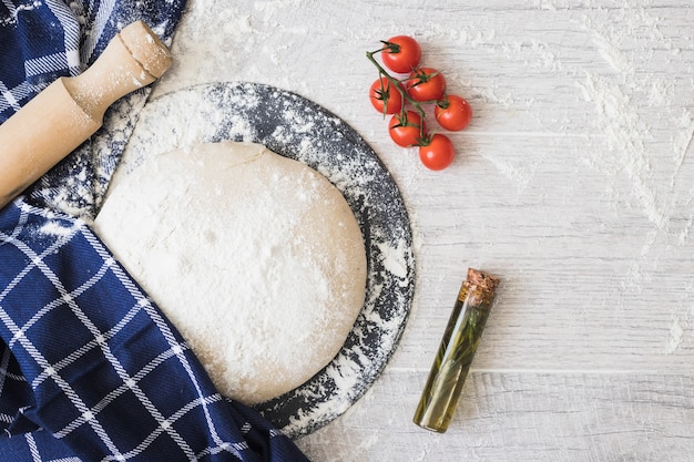 Flour dusted on dough bread; cherry tomatoes; rosemary and rolling pins on wooden plank Free Photo
