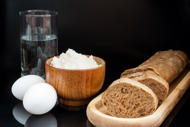 Flour, eggs, glass of water with fresh sliced baguette Premium Photo
