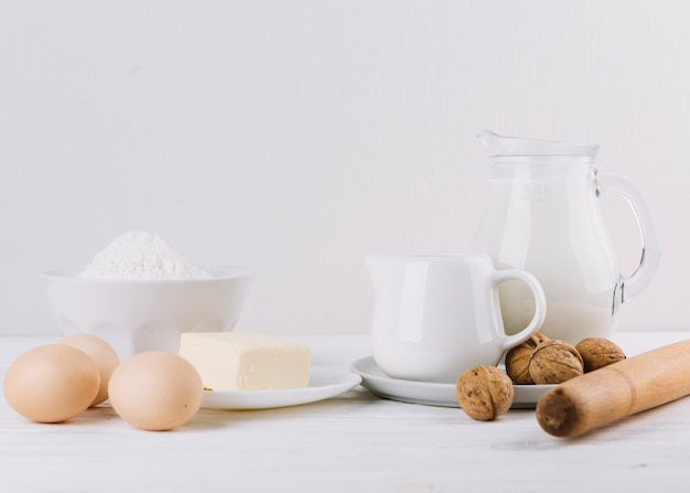 Flour; milk; eggs; cheese; rolling pin and walnuts on white backdrop for making pie Free Photo