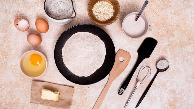 Мука на тарелке; яйцо; сливочное масло; молоко; овсяные отруби с лопаточкой; виски и мерная ложка на текстурированном фоне Бесплатные Фотографии