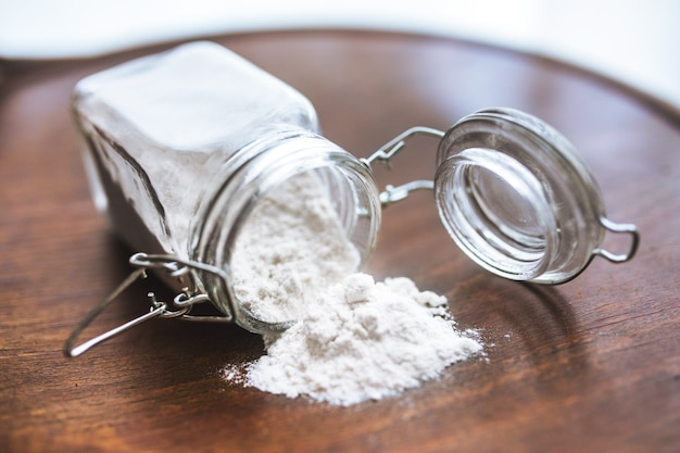 Flour on the table and in a glass jar Free Photo