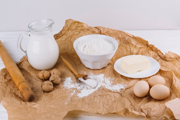 Flour; walnuts; eggs; cheese; rolling pin on brown crumpled paper Free Photo