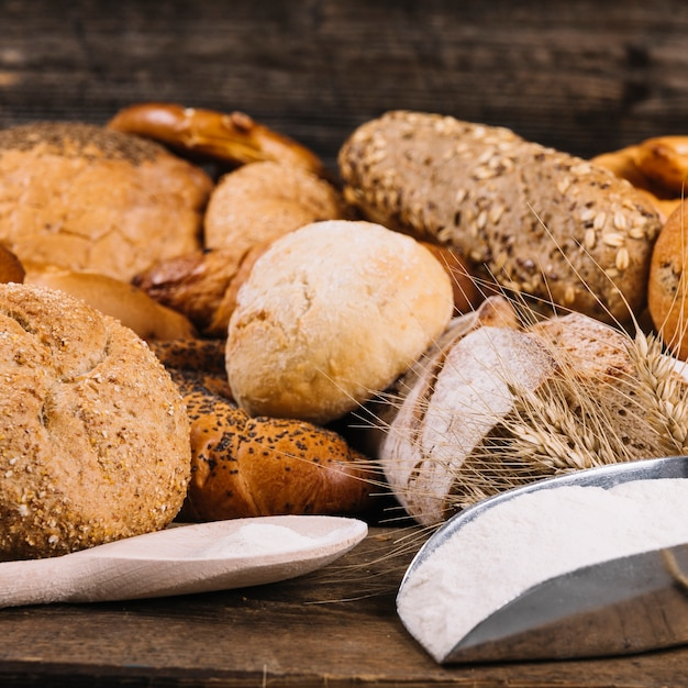Flour with baked whole grain breads on table Free Photo