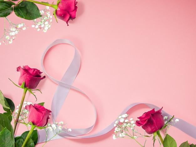 국제 여성의 날을위한 장식 흰색 8 모양 리본이 달린 장미로 만든 꽃 배경 프리미엄 사진