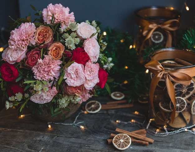 Flower bouquet, christmas ligths and cinnamon decoration sticks. Free Photo