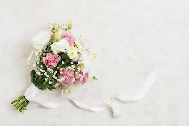 Flower bouquet tied with white ribbon on white backdrop Free Photo