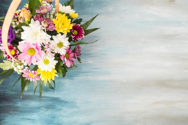 Flower bouquet in wicker basket placed on table Free Photo