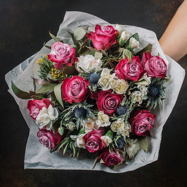 Flower bouquet with pink roses, blue thistle, mimosa and white roses Free Photo