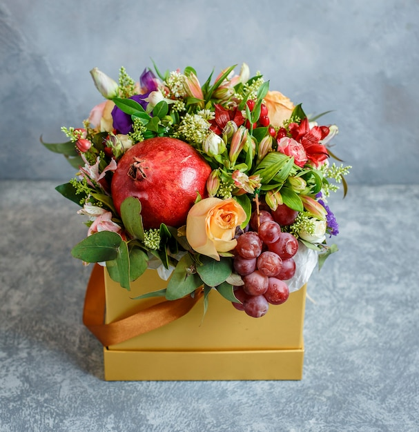 Flower bouquet with pomegranate, grape in yellow square box Free Photo