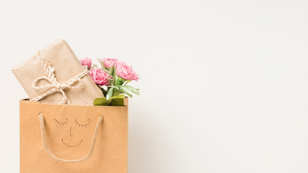 Flower bouquet and wrapped gift box in paper bag with hand drawn face isolated on white background Free Photo