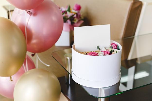 빈 카드, 장미 꽃 조성 꽃 상자. 어머니의 날, 여성의 날, 생일 및 인사말 카드, 디자인을위한 빈 공간이있는 선물 카드, 로고 선물 꽃다발. 축제 풍선 프리미엄 사진