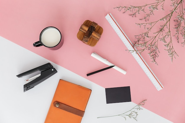 Flower branches, scale ruler, a cup of milk, pen, pencil, stapler, sketchbook and wooden block. Premium Photo