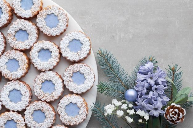Цветочное печенье linzer с голубой глазурью на светлом бетоне, украшенное голубыми цветами гиацинта, еловыми ветками и зеленью Premium Фотографии