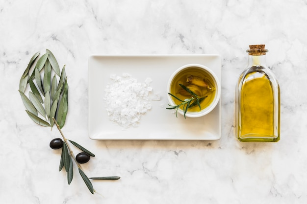 Flower made with olive and leaves with salt and oil in bowl and bottle Free Photo