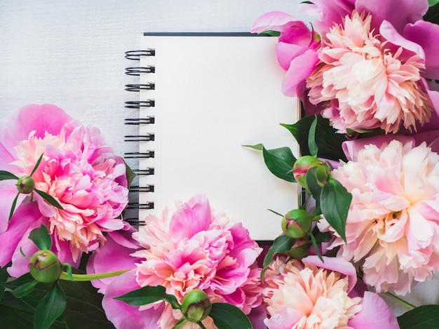 Flower pattern from blooming peony flowers and sketchbook Premium Photo