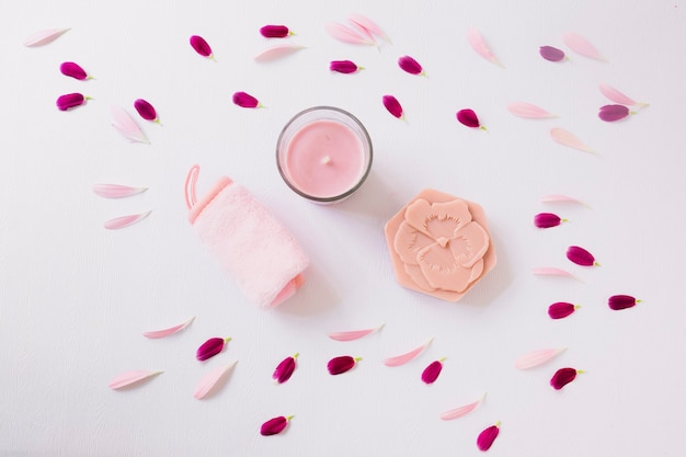 Flower petals around the rolled up soft napkin; candle and soap on white background Free Photo