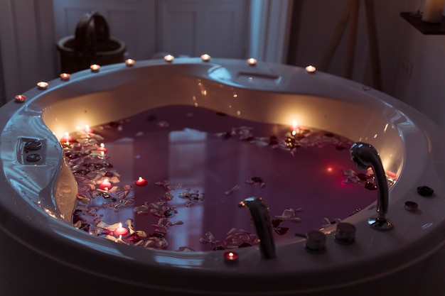 Flower petals in spa tub with waterand burning candles on edges Free Photo