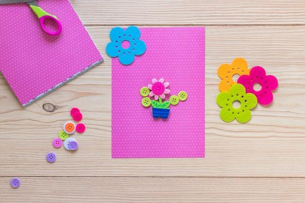 ピンクのカードで木のテーブルの上に飾られた花のポット 無料写真