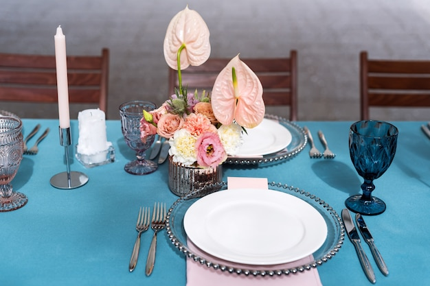 Flower table decorations for holidays and wedding dinner. table set for holiday wedding reception in outdoor restaurant. Premium Photo