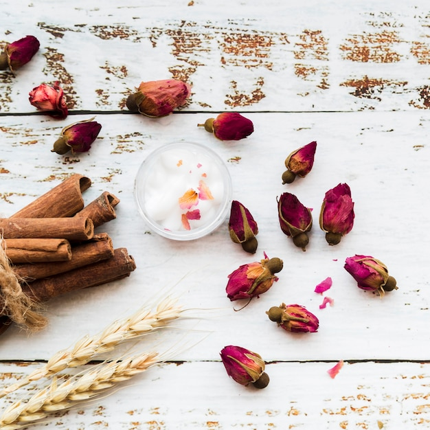 Flower tea of rose buds; cinnamon sticks; cotton in bowl; sheaf of wheat ears on white texture wooden plank Free Photo
