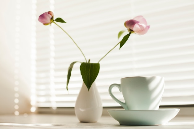 Flower vas and coffee cup with saucer near window blind Free Photo
