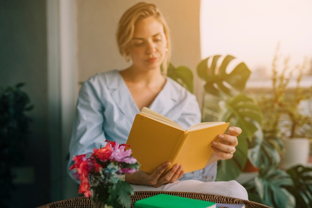 本を読んで若い美しい女性の前で花瓶 無料写真