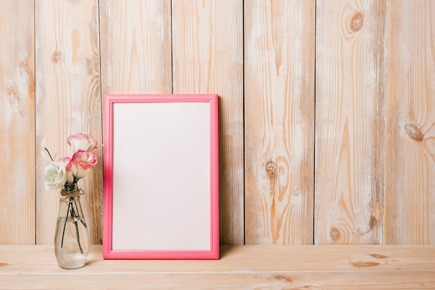 Flower vase near the white blank frame with pink border against wooden wall Free Photo
