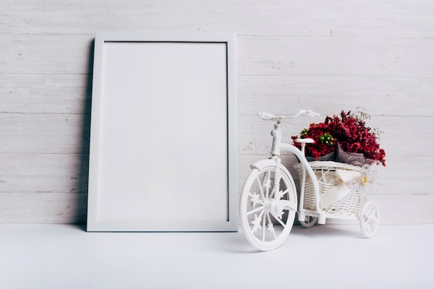 Flower vase with bicycle near the white blank frame on desk Free Photo