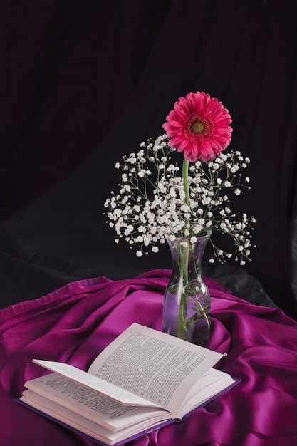 Flower with bloom twigs in vase near volume and violet textile in darkness Free Photo