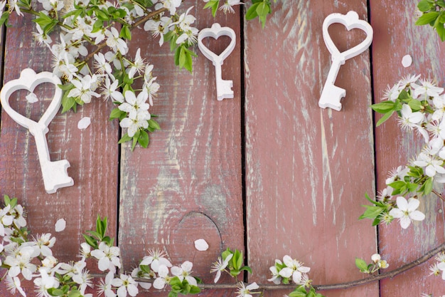 A flowering cherry branch and three wooden decorative keys Premium Photo