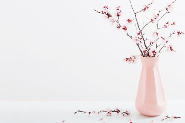 Flowering cherry branch in  vase on white background Premium Photo