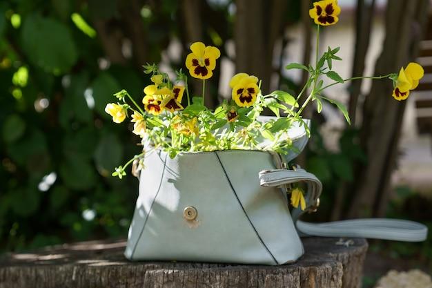 古い革の女性のバッグの屋外で小さな黄色い花を持つ顕花植物のパンジー。ゼロウェイスト。 Premium写真