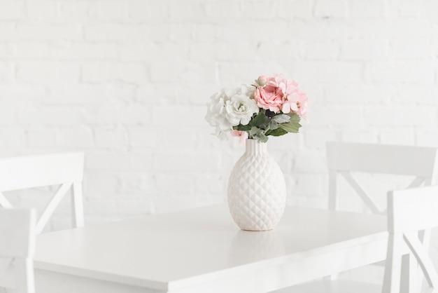 Flowering white vase on table against brick wall Premium Photo