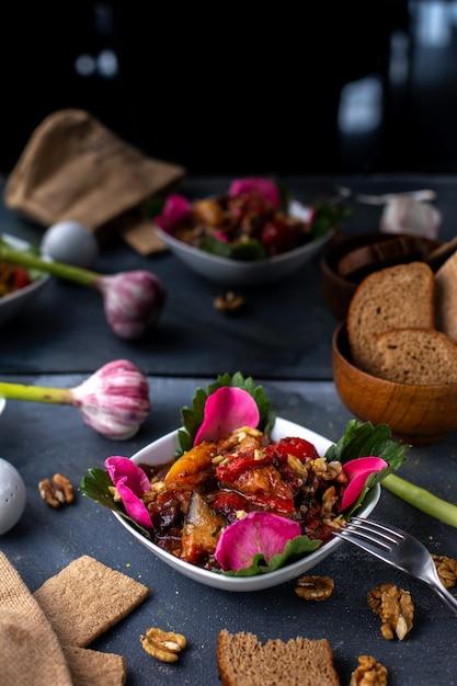 灰色の机の上の野菜と塩漬けに調理されたスライスされたチキンスライスと一緒に花 無料写真