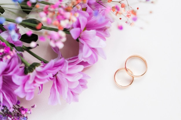 Flowers bouquet beside engagement rings Free Photo