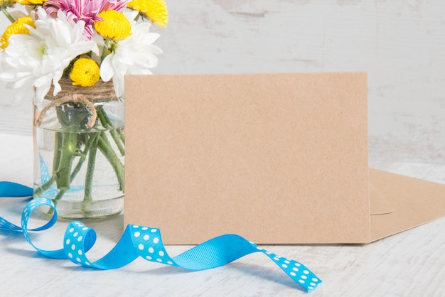Flowers bouquet in a jar vase with card note, envelope and blue ribbon on a white wood rustic background Premium Photo