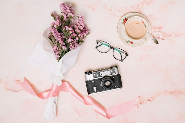 Flowers bouquet with camera and coffee on table Free Photo