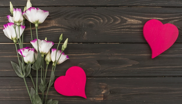 Flowers bouquet with hearts on wooden table Free Photo