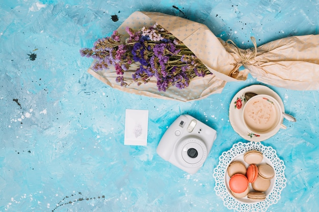 Flowers bouquet with instant camera, coffee cup and cookies Free Photo