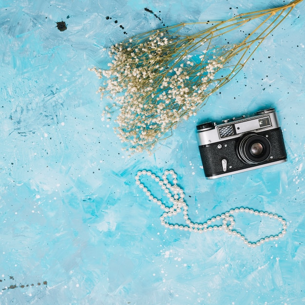 Flowers branches with camera and beads on table Free Photo